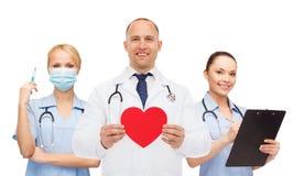 Grupa uśmiechać się lekarki z czerwonym kierowym kształtem Zdjęcie Royalty Free