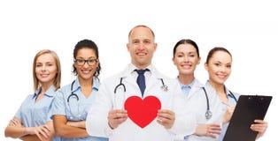 Grupa uśmiechać się lekarki z czerwonym kierowym kształtem Zdjęcie Stock