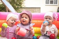Grupa uśmiechać się rozochocone śliczne dziecko dziewczyny bawić się wpólnie w rozrywka parku z zabawkami symbolizuje dziecko prz obraz royalty free