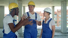 Grupa uśmiechnięci budowniczowie opowiada przy budową w hardhats zbiory