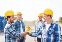 Grupa uśmiechnięci budowniczowie trząść ręki outdoors obraz stock