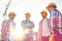 Grupa uśmiechnięci budowniczowie w hardhats outdoors zdjęcie royalty free