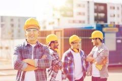 Grupa uśmiechnięci budowniczowie w hardhats outdoors zdjęcia royalty free