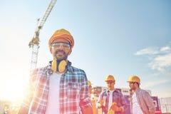 Grupa uśmiechnięci budowniczowie w hardhats outdoors obraz stock