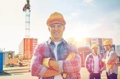 Grupa uśmiechnięci budowniczowie w hardhats outdoors obrazy stock