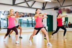 Grupa uśmiechnięci ludzie ćwiczy w gym Zdjęcia Royalty Free