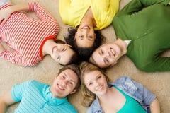 Grupa uśmiechnięci ludzie łgarskiego puszka na podłoga Obraz Royalty Free