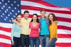 Grupa uśmiechnięci nastolatkowie nad flaga amerykańską zdjęcia royalty free