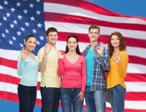 Grupa uśmiechnięci nastolatkowie nad flaga amerykańską zdjęcie royalty free