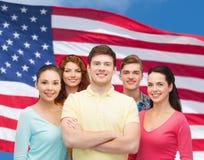 Grupa uśmiechnięci nastolatkowie nad flaga amerykańską fotografia stock
