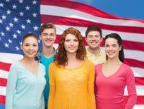 Grupa uśmiechnięci nastolatkowie nad flaga amerykańską obrazy royalty free