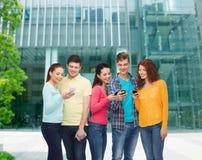 Grupa uśmiechnięci nastolatkowie z smartphones Obraz Royalty Free