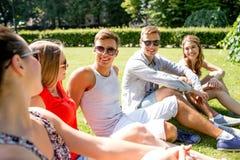 Grupa uśmiechnięci przyjaciele outdoors siedzi w parku Zdjęcie Royalty Free