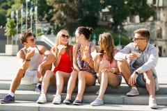 Grupa uśmiechnięci przyjaciele siedzi na miasto kwadracie Fotografia Royalty Free