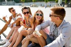 Grupa uśmiechnięci przyjaciele siedzi na miasto kwadracie Zdjęcia Royalty Free