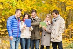 Grupa uśmiechnięci przyjaciele z pastylkami w parku Zdjęcia Royalty Free