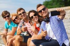 Grupa uśmiechnięci przyjaciele z smartphone outdoors Zdjęcia Royalty Free