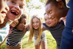Grupa uśmiechnięci ucznie opiera wewnątrz kamery obejmowanie zdjęcia stock