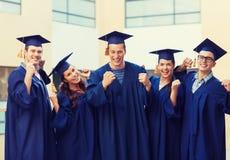 Grupa uśmiechnięci ucznie w mortarboards Obrazy Royalty Free