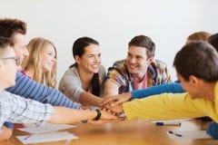 Grupa uśmiechnięci ucznie z ręką na wierzchołku fotografia stock