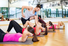 Grupa uśmiechnięte kobiety podnosi w gym robić siedzi Fotografia Stock