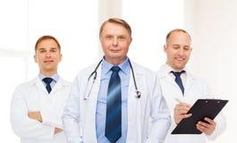 Grupa uśmiechnięte samiec lekarki w białych żakietach Fotografia Royalty Free