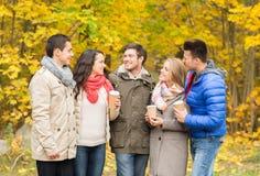 Grupa uśmiechnięty przyjaciel z filiżankami w parku Fotografia Stock