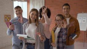Grupa ucznie 5 ludzi zabawa pomy?lni faceci w sali lekcyjnej ucznie pokazują ok znaka z ich ręką ucznie zdjęcie wideo