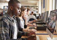 Grupa ucznie Używa komputery W szkoły wyższa bibliotece zdjęcia royalty free