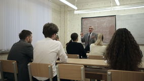 Grupa ucznie w sala lekcyjnej, słucha jako ich nauczyciel trzyma wykład zbiory wideo