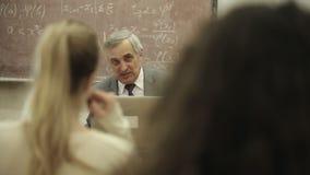 Grupa ucznie w sala lekcyjnej, słucha jako ich nauczyciel trzyma wykład zdjęcie wideo