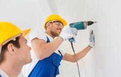 Grupa uśmiechnięci budowniczowie z świderem indoors Obrazy Stock