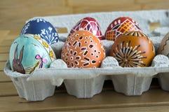 Grupa Wielkanocni jajka z różnorodnymi woskowatymi obrazami, małymi dziurami i obrazkami w papierowym jajecznym pudełku, obraz royalty free