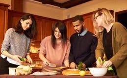 Grupa wielo- etniczni młodzi przyjaciele w kuchni przygotowywa dla przyjęcia Obrazy Royalty Free