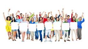 Grupa Wieloetniczne ręki Szeroko rozpościerać i mienie plakat Zdjęcie Stock