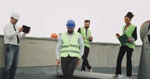 Grupa wieloetniczni pracownicy przy budową przerwa czasu jeden potomstw inżyniera tanczyć z podnieceniem będący ubranym hełm zdjęcie wideo