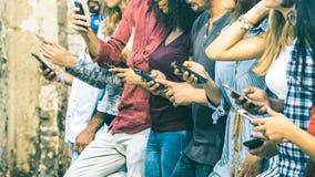Grupa wielokulturowi przyjaciele używa mobilnego mądrze telefon