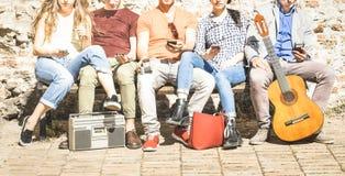 Grupa wielokulturowi przyjaciele używa smartphone na miastowym tle zdjęcie stock