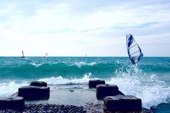Grupa windsurfers na deskach w falistym morzu z molem na wybrzeżu Fotografia Royalty Free
