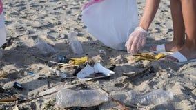 Grupa wolontariuszi czyści w górę plaży linii Kobieta podnosi plastikową butelkę i rzuca w torbę zbiory