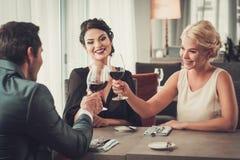 Grupa zamożni ludzie clinking szkła czerwone wino w restauraci Zdjęcia Stock