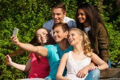 Grupo étnico multi de amigos en un parque que toma el selfie Foto de archivo libre de regalías