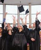 Grupo étnico multi de estudiantes graduados que lanzan los sombreros fotos de archivo libres de regalías