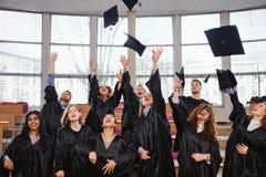 Grupo étnico multi de estudiantes graduados que lanzan los sombreros fotografía de archivo