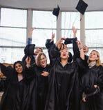 Grupo étnico multi de estudiantes graduados que lanzan los sombreros foto de archivo libre de regalías