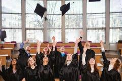 Grupo étnico multi de estudiantes graduados que lanzan los sombreros fotografía de archivo libre de regalías