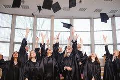 Grupo étnico multi de estudiantes graduados que lanzan los sombreros imagen de archivo libre de regalías