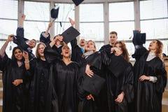 Grupo étnico multi de estudiantes graduados que lanzan los sombreros imágenes de archivo libres de regalías