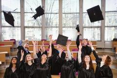 Grupo étnico multi de estudiantes graduados que lanzan los sombreros imagen de archivo