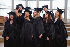 Grupo étnico multi de estudiantes graduados que toman el selfie fotos de archivo
